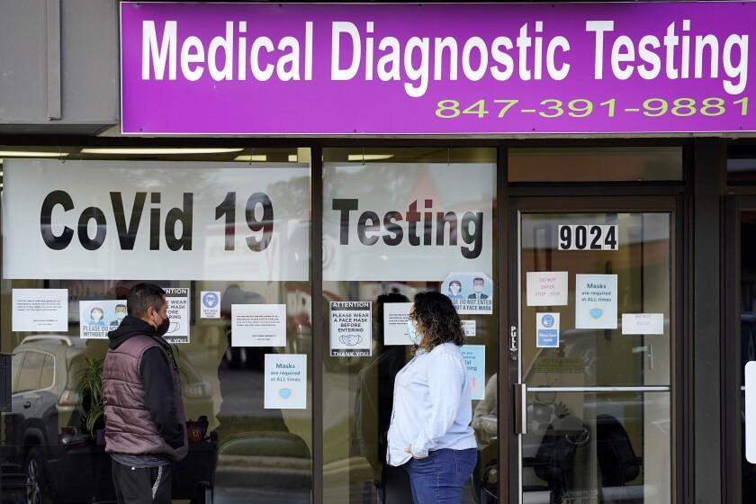 Una empleada de Exam Corp Lab habla con un paciente formado para realizarse una prueba de COVID-19