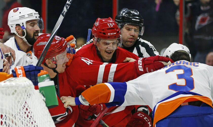 Carolina Hurricanes' Joakim Nordstrom (42) of Sweden, and Andrej Nestrasil (15) of the Czech Republic, tussle with New York Islanders' Travis Hamonic (3) during the second period of an NHL hockey game, Saturday, Feb. 13, 2016, in Raleigh, N.C. (AP Photo/Karl B DeBlaker)