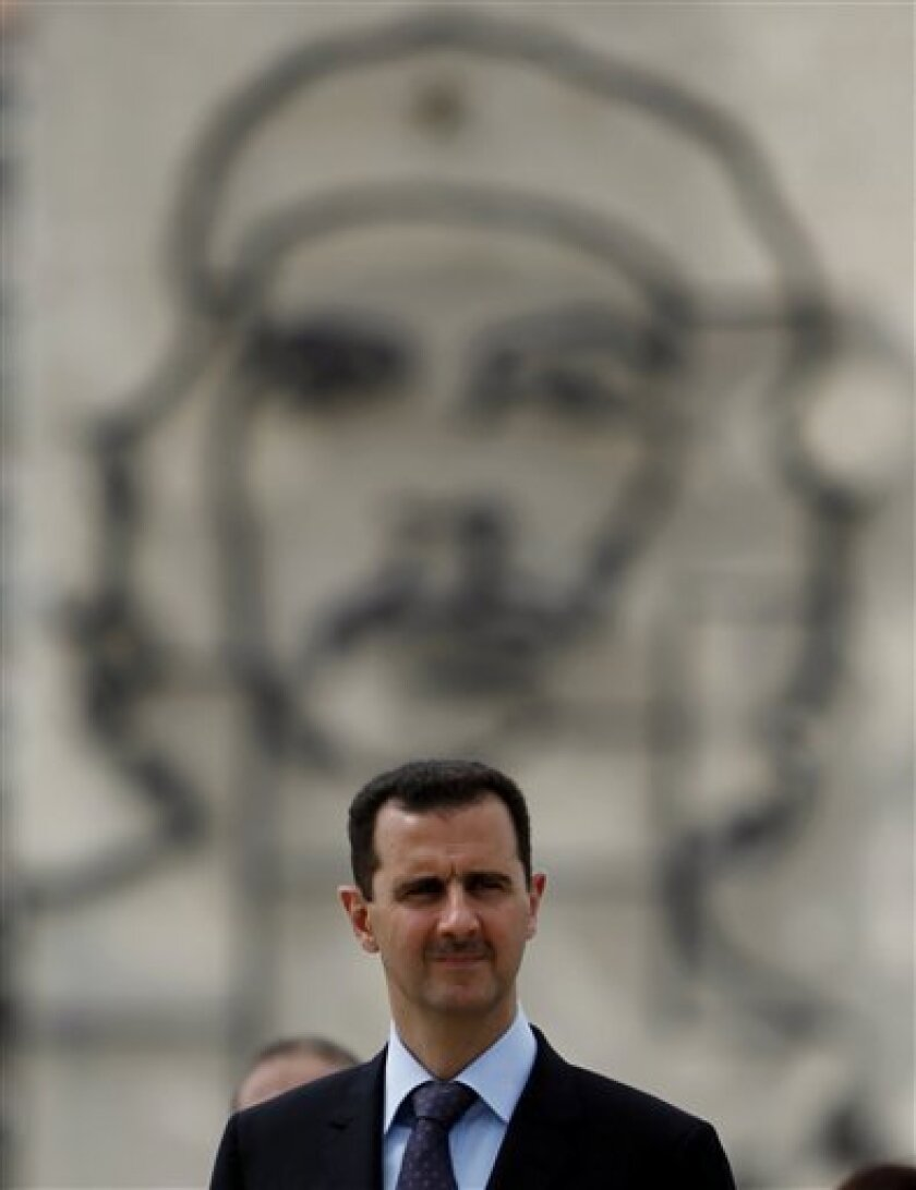 """Syria's President Bashar al-Assad stands in front of an image of Cuba's revolutionary hero Ernesto """"Che"""" Guevara as he attends a wreath-laying ceremony at the Jose Marti monument in Havana, Monday June 28, 2010.  Al-Assad is in Cuba for an official visit. (AP Photo/Javier Galeano)"""