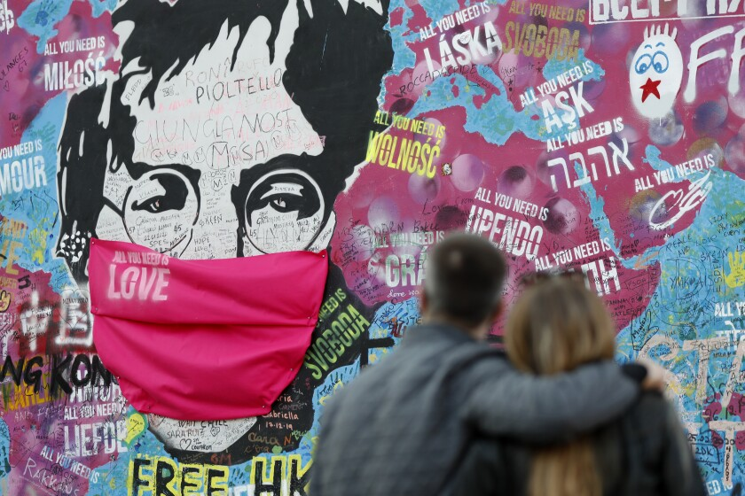 """FILE - A couple look at the """"Lennon Wall"""" with a face mask attached to the image of John Lennon, in Prague, Czech Republic, on April 6, 2020. Like so many other events in the year of coronavirus, an annual tribute to John Lennon held in its adopted city of New York will go online. The five-hour event will be streamed for free on Lennon's birthday, October 9, starting at 7 p.m. Eastern time on the LennonTribute.org website. It will feature recorded performances from Patti Smith, Rosanne Cash, Natalie Merchant, Jackson Browne, Jorma Kaukonen and others. (AP Photo/Petr David Josek)"""