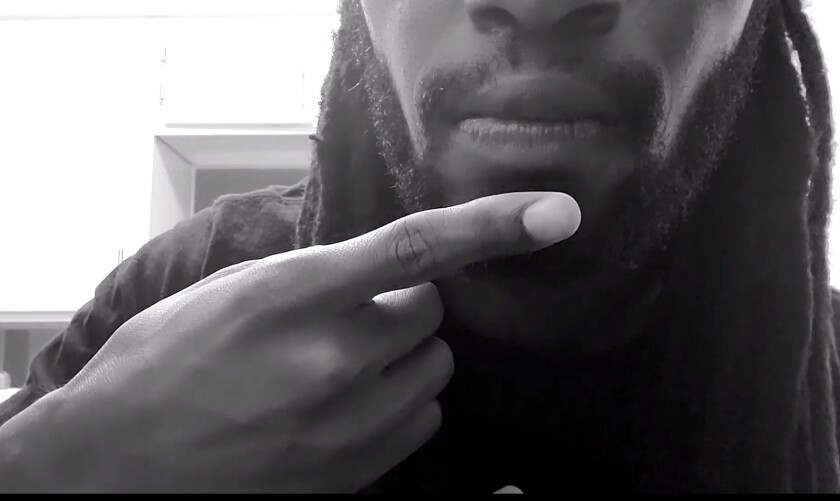 """A close-up of actor Malcom Stokes taps his chin, making the ASL symbol for """"say it"""" or """"speak it."""""""