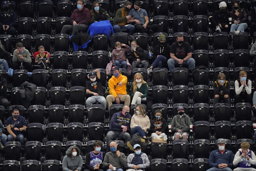 Small groups of Utah Jazz fans surrounded by empty seats watch a game against the Phoenix Suns on Thursday in Salt Lake City.