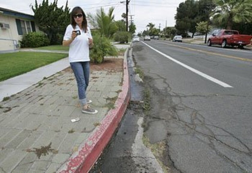 Julie Olson, an inspector for the San Diego Water Department, checked out two areas near San Diego State University for water runoff.  (John Gibbins / Union-Tribune)