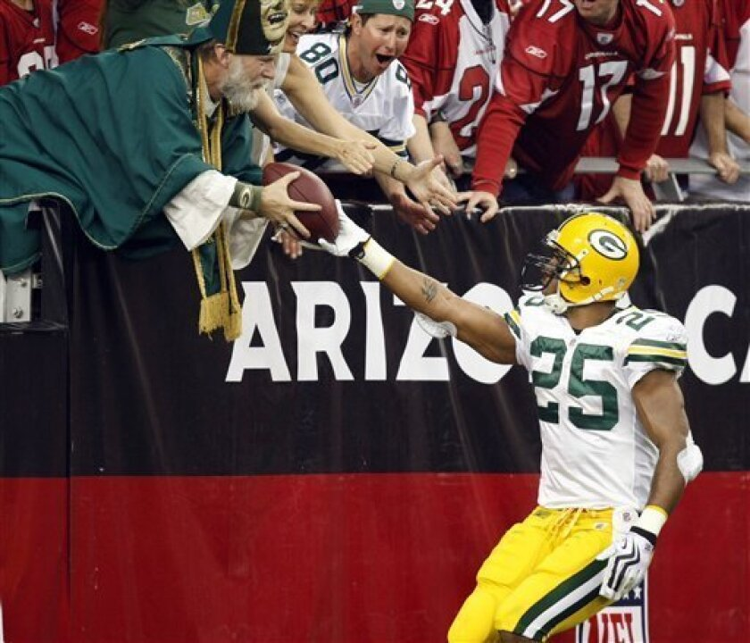 Green Bay Packers running back Ryan Grant (25) hands the football to a Packers fan after scoring a touchdown against the Arizona Cardinals during the first half on an NFL football game Sunday, Jan. 3, 2010, in Glendale, Ariz. (AP Photo/Matt York)