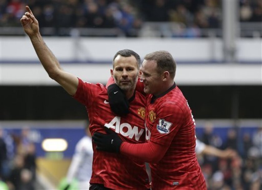 Manchester United's Ryan Giggs, left, celebrates with his teammate Wayne Rooney, right, after he scored against Queens Park Rangers, during their Premier League soccer match at Loftus Road ground in London, Saturday, Feb. 23, 2013. Manchester United won the match 2-0. (AP Photo/Lefteris Pitarakis)