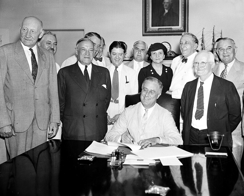 President Franklin Roosevelt signs the Social Security Act on Aug. 14, 1935. Behind him is the program's godmother, Labor Secretary Frances Perkins. A new technical report leaves one less reason to attack the program.