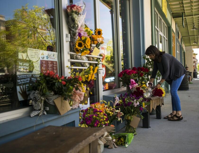 Una mujer deposita un ramo de flores en un altar improvisado para recordar a la copropietaria de una floristería, Jillian Johnson, en Lafayette. Johnson es una de las víctimas de la balacera mortal. (Paul Kieu/The Daily Advertiser via AP)