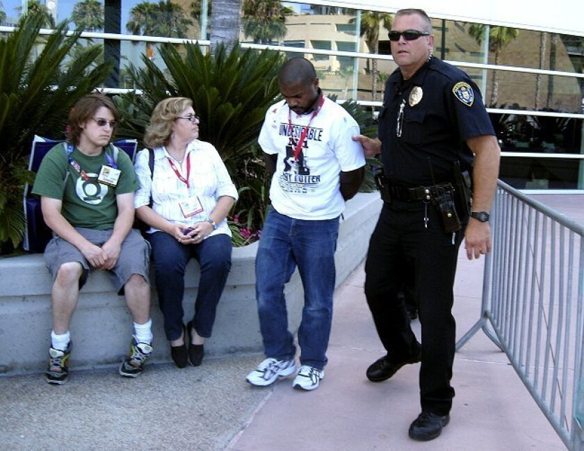Stabbing suspect is led away by a police officer at Comic-Con.