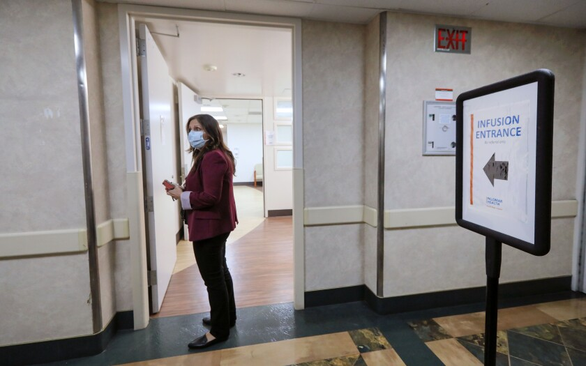 Palomar Health RN Valerie Martinez heads to the monoclonal antibody infusion station at Palomar Medical Center.
