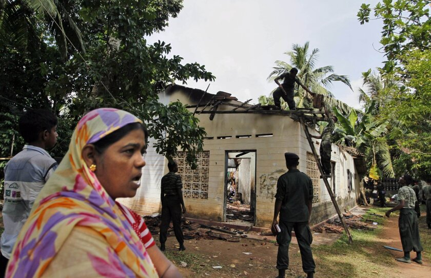 In this Friday, June 27, 2014 photo, a Sri Lankan Muslim woman watches as army soldiers salvage damaged household items from the debris of a burnt house in Darga Town in Aluthgama, about 50 kilometers (31 miles) south of Colombo, Sri Lanka. The onslaught by the Bodu Bala Sena (BBS), a hardline Buddhist group, killed two Muslims in the worst religious violence Sri Lanka has seen in decades. (AP Photo/Eranga Jayawardena)