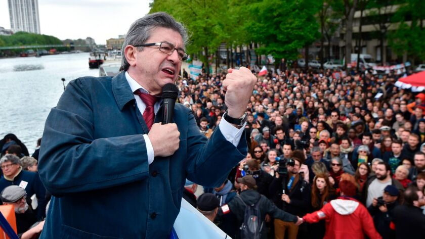 French presidential candidate Jean-Luc Melenchon gives a speech aboard a barge Monday in Paris, part of campaign meetings along the Seine river.
