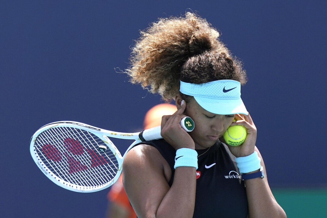 Naomi Osaka, holding tennis racket and ball, leans her head forward and presses her fingers against her ears.