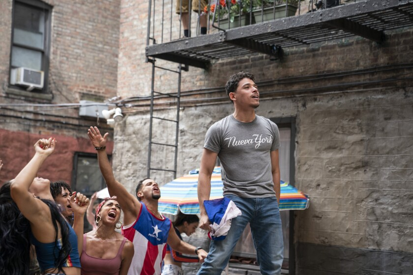 """Anthony Ramos dances on a table in an alley wearing a grey T-shirt that reads """"Nueva York"""""""