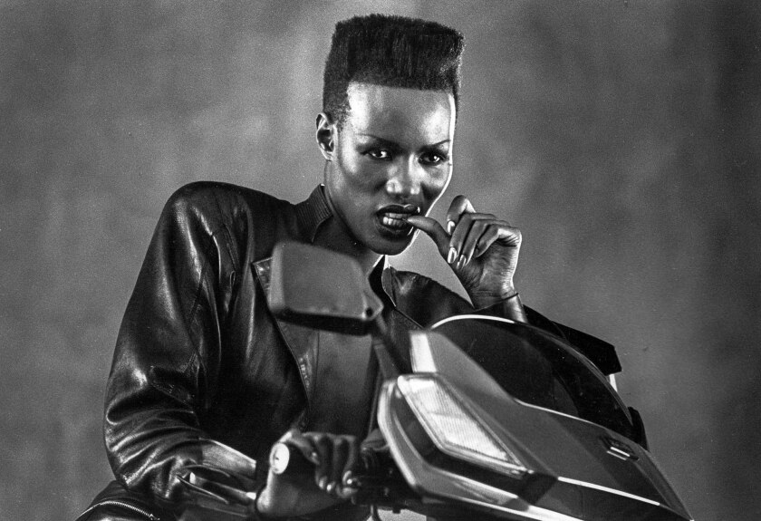 1985: Grace Jones poses for Los Angeles Times staff photographer Larry Davis during a break in the shooting of a Honda motor scooter commercial.