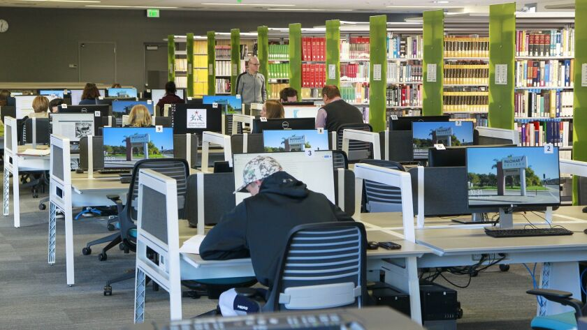Students work in the reference library and computer room on the first floor of the new library at Palomar College in San Marcos.