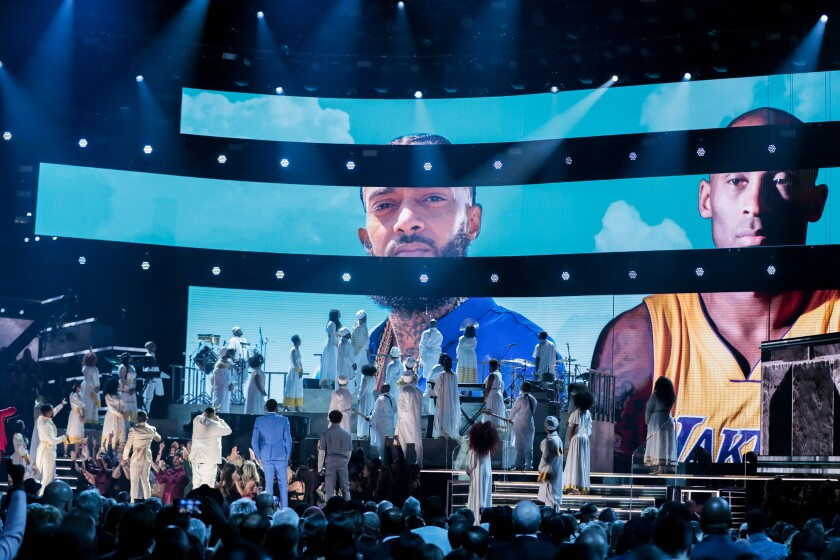 A tribute to Nipsey Hussle and Kobe Bryant is displayed as YG, John Legend, DJ Khaled, Meek Mill, Roddy Ricch, Kirk Franklin and others stand on stage at the Grammy Awards on Sunday.