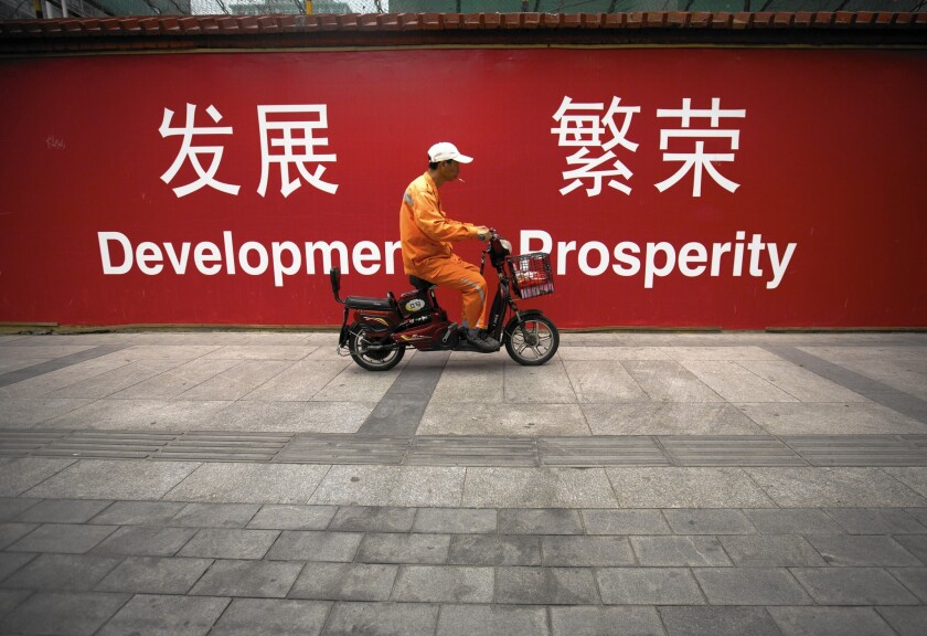 "China's total debt has nearly quadrupled since 2007, to more than $28.2 trillion, according to the McKinsey Global Institute. Above, a maintenance worker rides a scooter past banners reading ""Development"" and ""Prosperity"" in English and Chinese on a Beijing street."