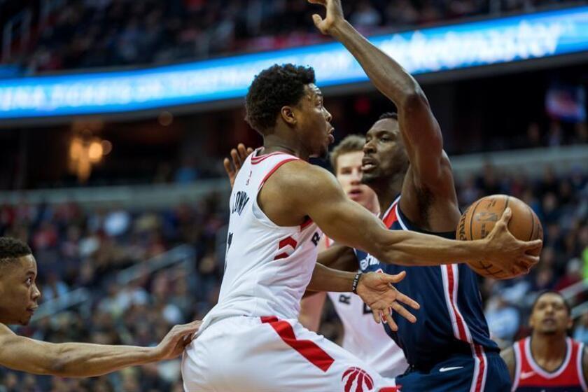 El defensa Kyle Lowry (c) de Toronto Raptos controla el balón durante un partido de baloncesto de la NBA ante los Washington Wizards, en el Capitol One Arena de Washington, DC (EE.UU.). EFE