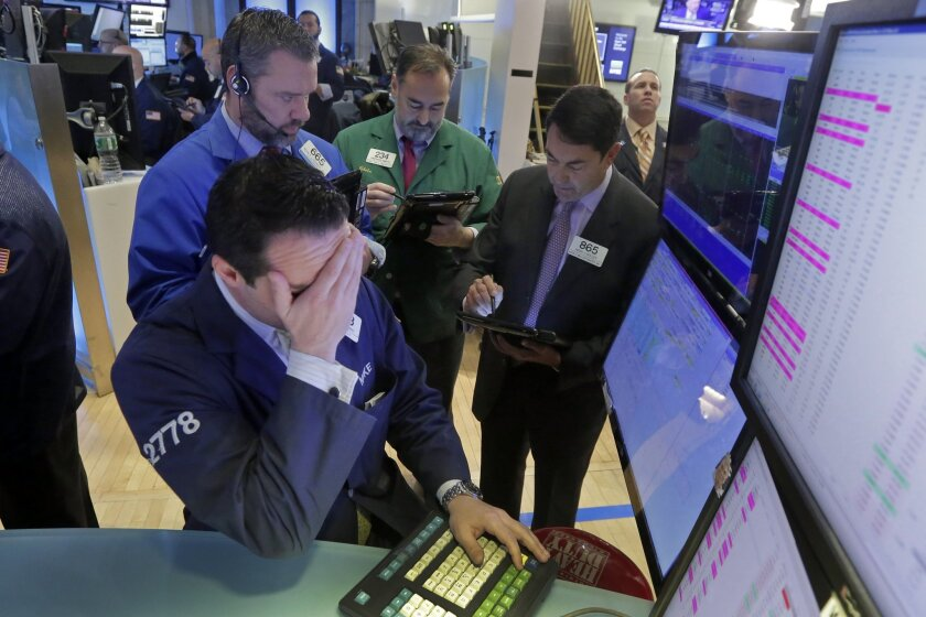 FILE - In this Feb. 1, 2016, file photo, specialist Michael Gagliano, foreground, works with traders at his post on the floor of the New York Stock Exchange. A strengthening job market, low gasoline prices and rising home values are all helping consumers to spend more, even though stock markets on
