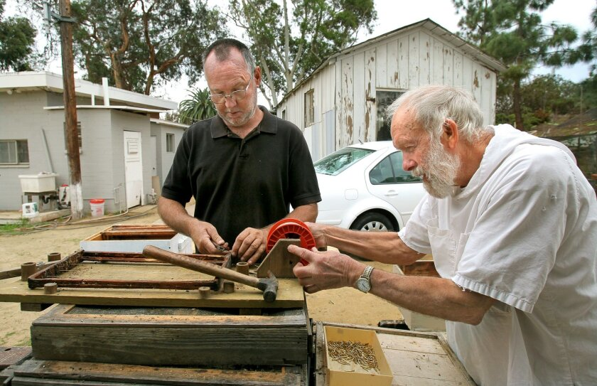 Brother Blaise Heuke, at right, gets assistance repairing the wooden frames for his beehives from volunteer assistant Joseph Strawbridge, at left, at his workshop.
