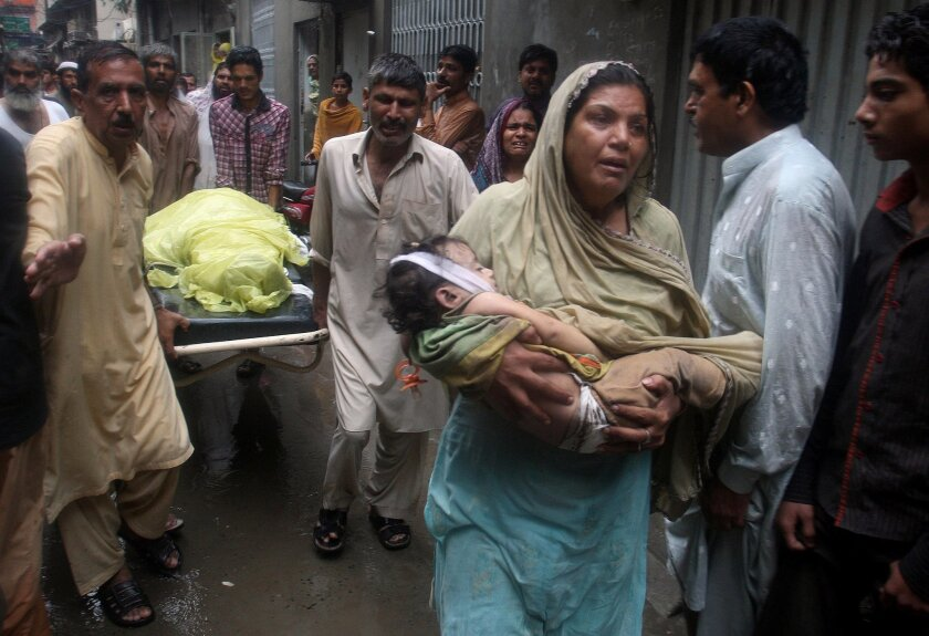 A woman carries the lifeless body of baby girl as others transport the body of a man both killed after the roof top of their home collapsed from heavy rain in Lahore, Pakistan, Thursday, Sept. 4, 2014. Many people have been killed and scores injured in accidents caused by heavy rain in Punjab province, local media reported on Thursday. (AP Photo/K.M. Chaudary)