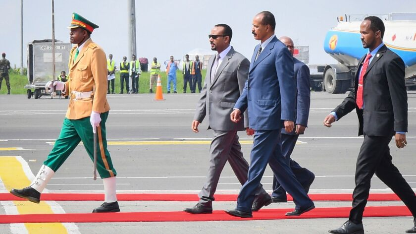 President of Eritrea Isaias Afwerki, second from right, walks with Ethiopian Prime Minister Abiy Ahmed, second from left, upon his arrival at Bole International Airport in Addis Ababa, Ethiopia, on July 14, 2018.