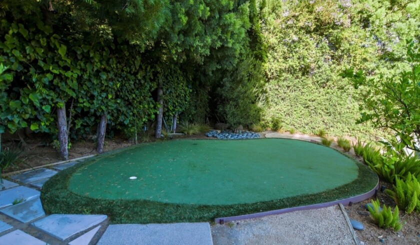The property listed by Ryan Miller and Noureen DeWulf includes their own personal putting green.