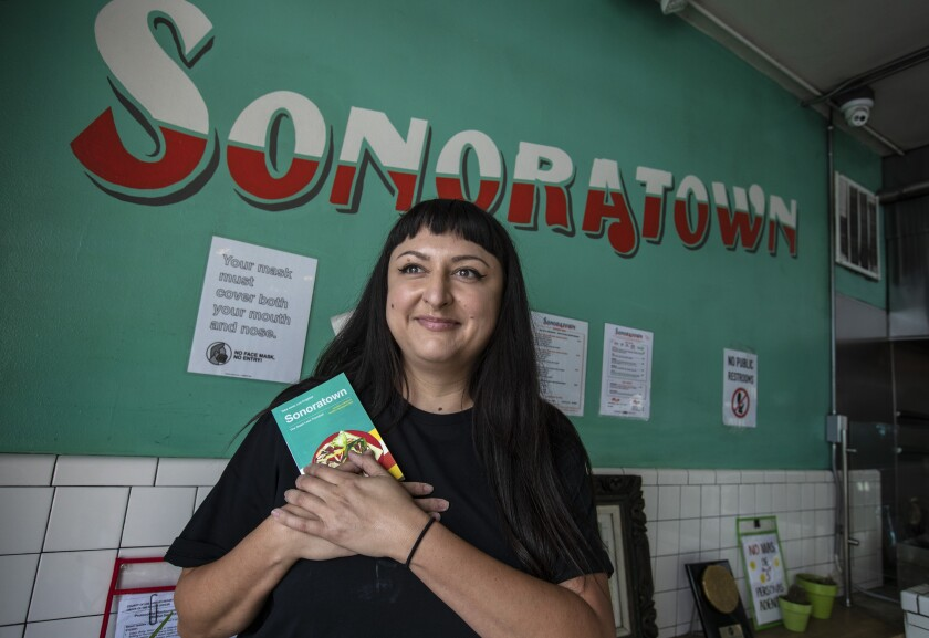 "A smiling woman holds a book. Behind her is a green wall with the word ""Sonoratown"" in red and white."