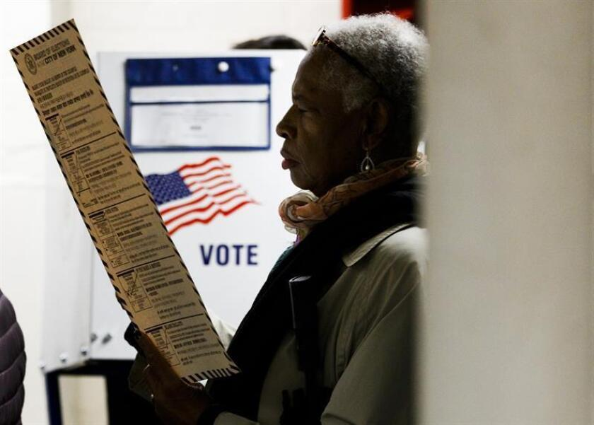 A woman reads over her ballot as people cast votes in the 2018 midterm general election at a polling site in the Bronx, New York, USA, 06 November 2018. Voters across the nation are selecting who will represent them on local, state and national levels. EPA-EFE/JUSTIN LANE