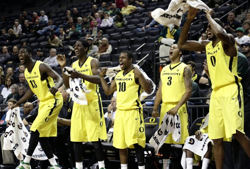 The Oregon bench celebrates during the second half of an NCAA college basketball game against Cal Poly in Eugene, Ore., Sunday, Dec. 1, 2013. From left are Richard Armadi, Damyean Dotson, Johnathan Loyd, Joseph Young and Mike Moser. Oregon won 82-61. (AP Photo/Don Ryan)