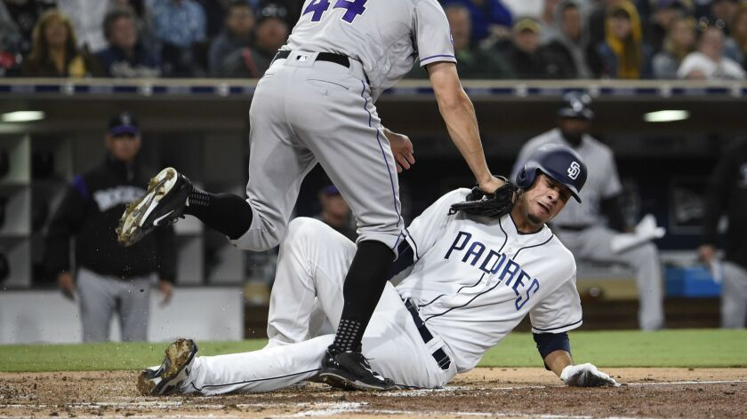 Padres pitcher Joey Lucchesi is tagged out at the plate by Tyler Anderson of the Colorado Rockies during the third inning of Monday's game at Petco Park.