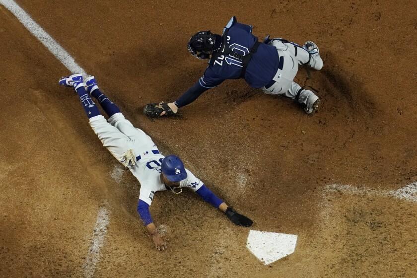 Mookie Betts, de los Dodgers de Los Ángeles, anota al evadir el lance del receptor de los Rays de Tampa Bay Mike Zunino