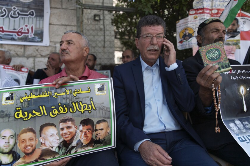 """Qadoura Fares, center, attends a protest supporting prisoners, while a fellow protester carries a poster with pictures of the six Palestinian prisoners who escaped from an Israeli jail that says """"heroes of the freedom tunnel,"""" in the West Bank city of Ramallah, Tuesday, Sept. 14, 2021. Fares, head of the Prisoners Club, which represents current and former Palestinian prisoners, said they are all """"freedom fighters."""" (AP Photo/Nasser Nasser)"""
