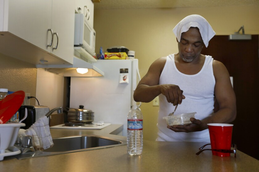 Maurice Caldwell makes oatmeal for breakfast in the hotel room he calls home in Sacramento.