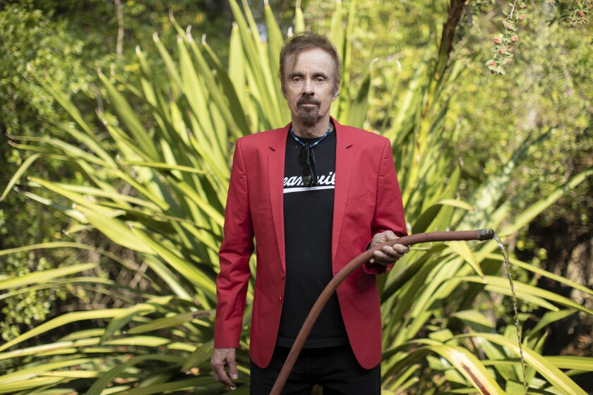 Author T.C. Boyle stands amid plants holding a watering hose.