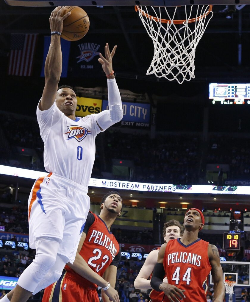 Oklahoma City Thunder guard Russell Westbrook (0) shoots in front of New Orleans Pelicans forward Anthony Davis (23) and Dante Cunningham (44) in the first quarter of an NBA basketball game in Oklahoma City, Thursday, Feb. 11, 2016. (AP Photo/Sue Ogrocki)
