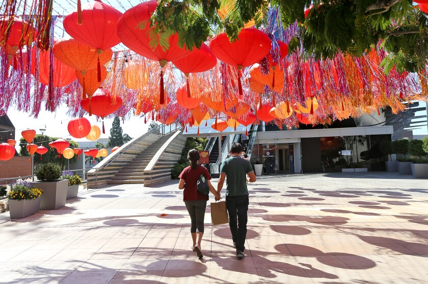 Shoppers walk under a ceiling of red lanterns that mark the Autumn Harvest Festival going on at South Coast Plaza.