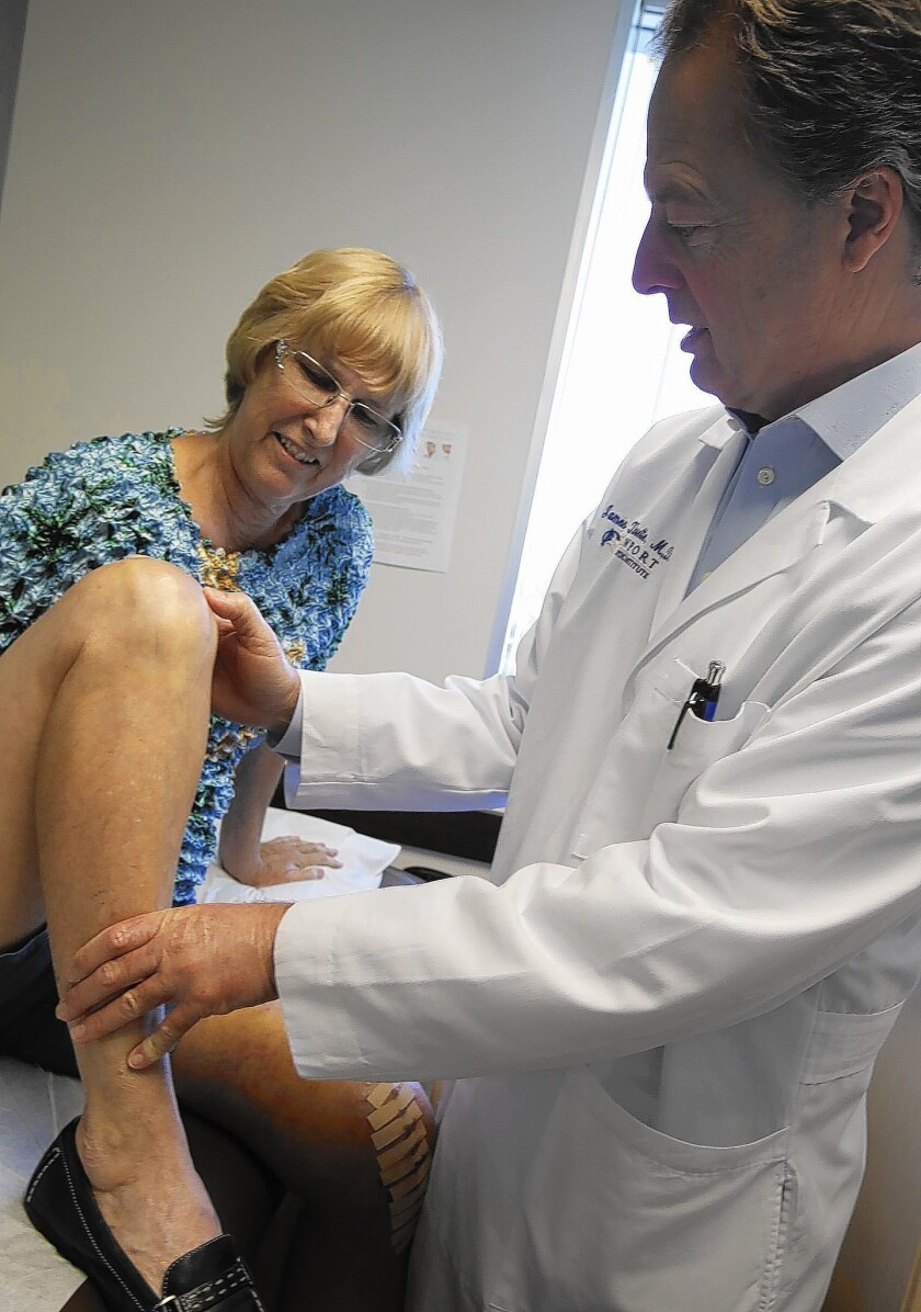 Dr. James Cailouette, surgeon in chief for Hoag Orthopedic Institute in Irvine, examines patient Carolyn Rondou's right knee, which was replaced with a mechanical joint.