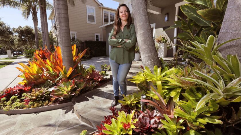 Portrait of Juliana Raposo in front of her house with Aechmea Blanchetiana Bromeliads at left, and at right are Neoregelia Bromeliads.