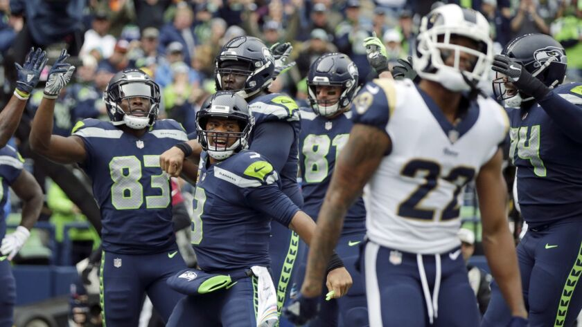 Seattle Seahawks quarterback Russell Wilson (3) celebrates next to Los Angeles Rams cornerback Marcu