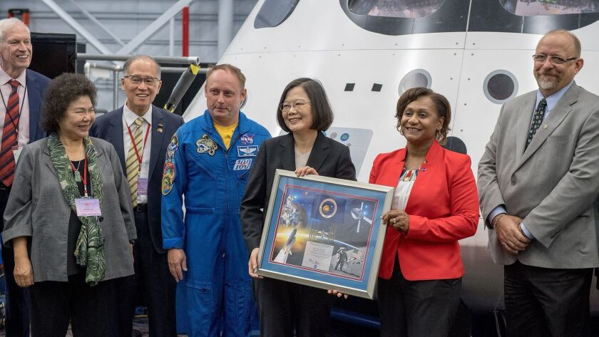 Taiwanese President Tsai Ing-wen, center, accompanied by U.S. astronaut Edward Michael Fincke and Vanessa E. Wyche, in red, deputy director of NASA's Johnson Space Center.