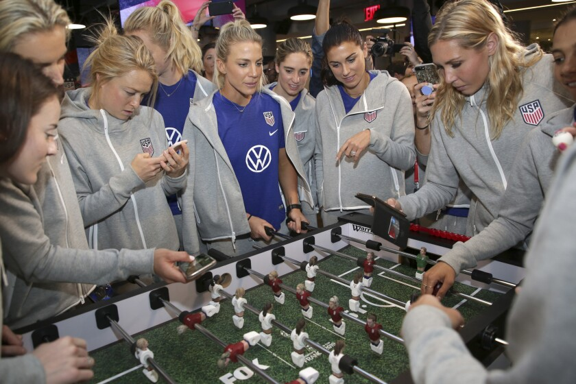Members of the United States women's national soccer team react while while playing a foosball table