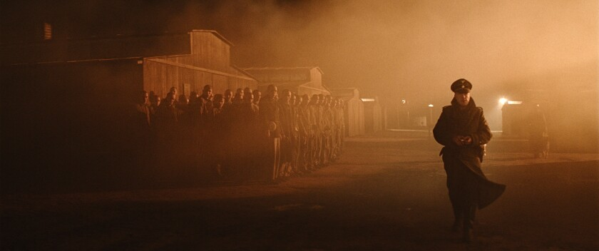 """A Nazi officer walks past prisoners in a World War II concentration camp in the movie """"The Auschwitz Report."""""""