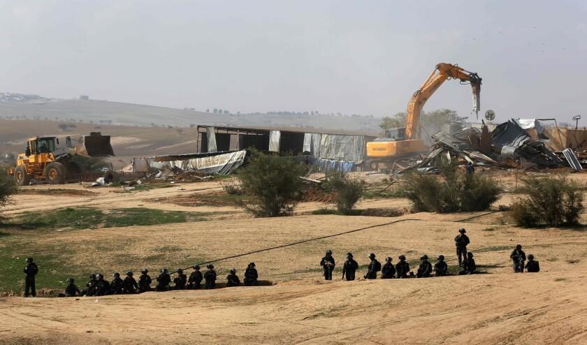 Israeli policemen stand guard as bulldozers demolish homes in the Bedouin village of Um al Hiran.