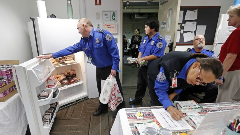 TSA workers look through a refrigerator stocked with meat during a Second Harvest Food Bank Orange C