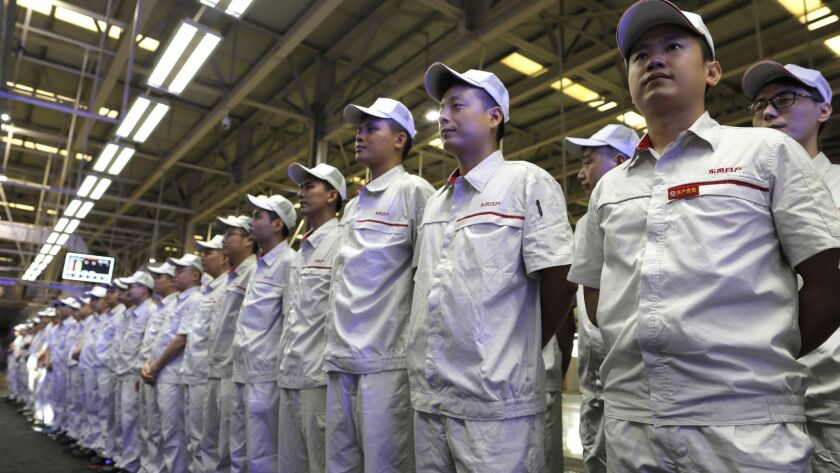 Workers of the Dongfeng Nissan attend the ceremony launching the Nissan Sylphy Zero Emission, the Ni