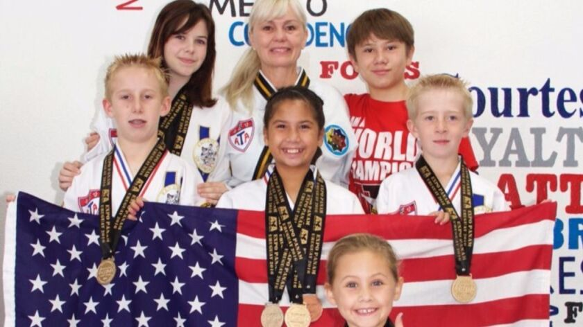 Six Church's ATA Martial Arts students — back row from left, Cameron Twomey, instructor Patricia Church and Kane Church; middle row from left, James Knee, Grace Dabir and Luke Knee; front, Channah Zeitung — won titles at the 2016 Pam American Taekwondo Championships in Uruguay.