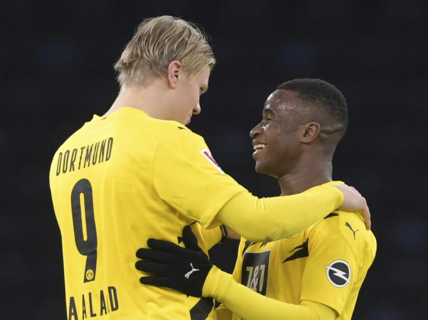 Erling Haaland (izquierda) y Youssoufa Moukoko, del Borussia Dortmund, se abrazan luego del partido que su equipo ganó al Hertha Berlín el sábado 21 de noviembre de 2020 (Soeren Stache/dpa via AP)