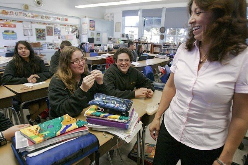 Teacher Rose Navarro (right) at St. Mary Star of the Sea School in Oceanside talks with her students Molly Weber (left) and Nicholas Escandon about what they will see and do during their trip to Washington, D.C., for the inauguration.