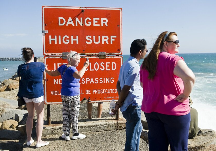 A sign warns visitors of high surf as they stand on the jetty protecting Dana Point Harbor on Saturday afternoon Sept. 6, 2014 in Dana Point, California. Hurricane Norbert in Baja California is responsible for the high surf. Norbert weakened Saturday night to a Category 1 storm with winds of up to 85 mph (140 kph). Though staying away from land, it was near enough to the coast to drench fishing villages and resorts, and pound beaches. (AP Photo/The Orange County Register, Nick Agro)